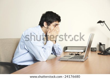 Businessman looking at his laptop computer screen as if faced with a big problem - stock photo