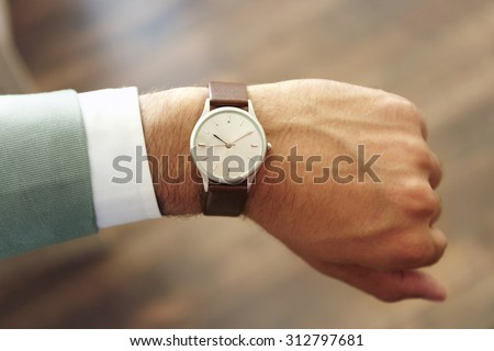 Businessman looking at his watch in office - stock photo