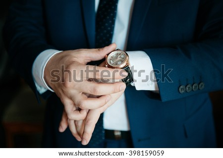 businessman looking at his watch on his hand, watching the time - stock photo