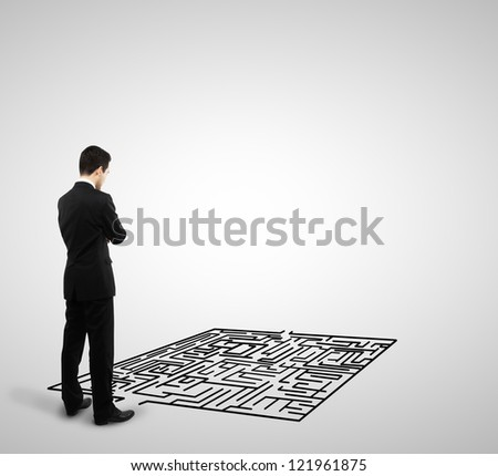 businessman looking at labyrinth on a white background - stock photo