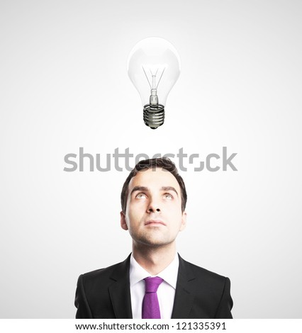 businessman looking at lamp on white background