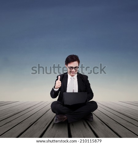 Businessman looking at laptop with ok sign - stock photo