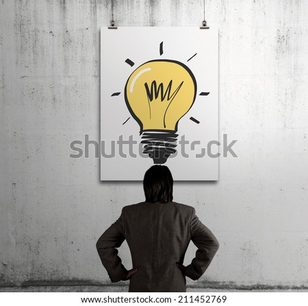 businessman looking at light bulb in art frame on the wall as concept - stock photo
