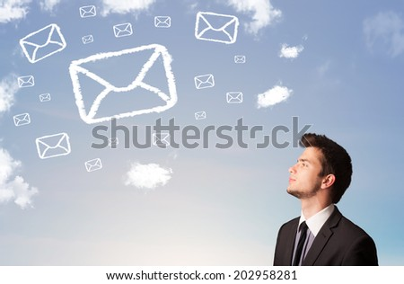 Businessman looking at mail symbol clouds on blue sky - stock photo