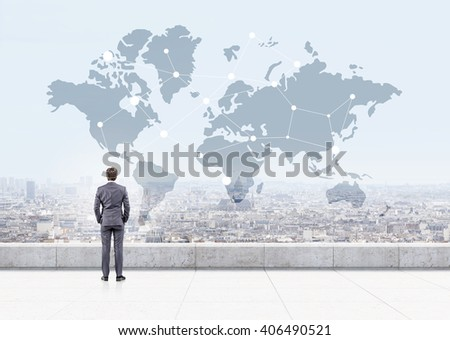 Businessman looking at map with networking system on cityscape background - stock photo