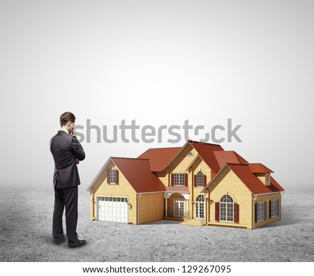 businessman looking at model house - stock photo