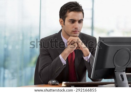 Businessman looking at monitor screen in office - stock photo