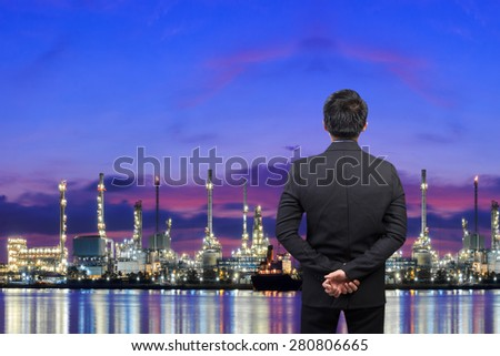 Businessman looking at oil refinery petrochemical industrial plant at twilight - stock photo