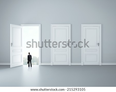 businessman looking at opened door in room - stock photo
