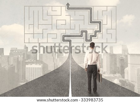 Businessman looking at road with maze and solution concept - stock photo