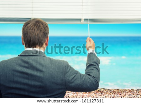 Businessman looking at sea out of the window - stock photo