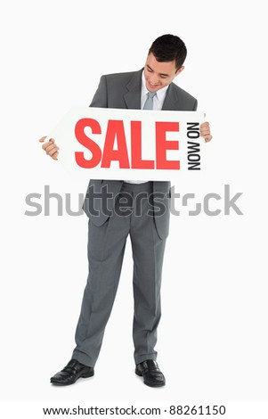 Businessman looking at signboard in his hands against a white background