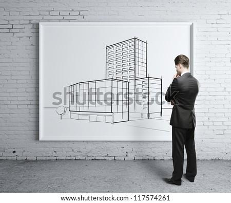 businessman looking at skyscraper on desk - stock photo