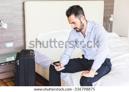 Businessman looking at smart phone in his hotel room. He is sitting on the bed, wearing black trousers and a light blue shirt. Grave expression, business and work issues concepts. - stock photo