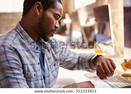 Businessman Looking At Smart Watch In Design Office - stock photo