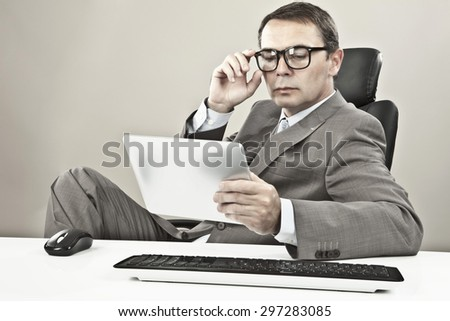 Businessman looking at tablet pc against grey background