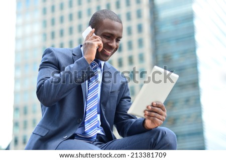 Businessman looking at tablet while talking on cell phone - stock photo