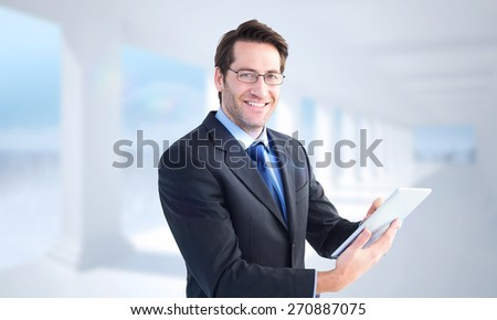 Businessman looking at the camera while using his tablet against bright white room with columns - stock photo