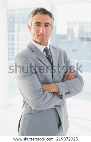 Businessman looking at the camera with his arms folded - stock photo