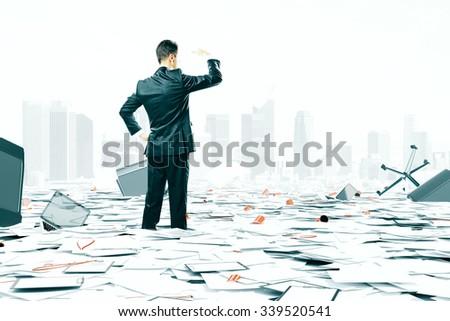 Businessman looking at the horizon among office stuff chaos - stock photo