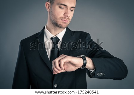 Businessman looking at the time on his wrist watch against dark background. - stock photo