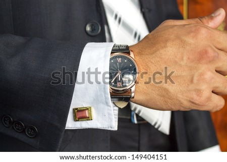 businessman looking at the watch, high key, focus on the watch - stock photo