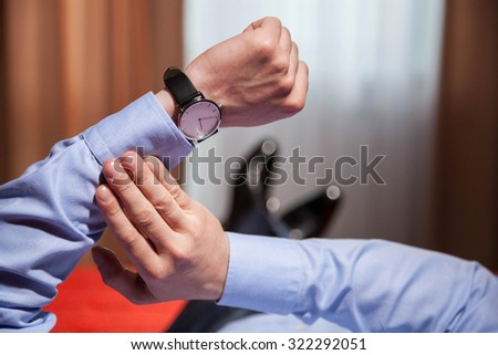 Businessman looking at the wristwatch and lying on the bed, closeup shot - stock photo