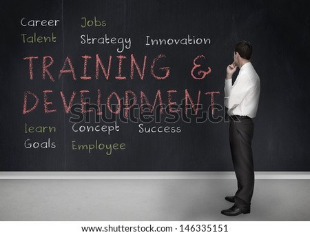 Businessman looking at training and development terms written on a blackboard  - stock photo