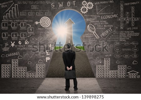 Businessman looking at up arrow sign through a keyhole with written blackboard - stock photo