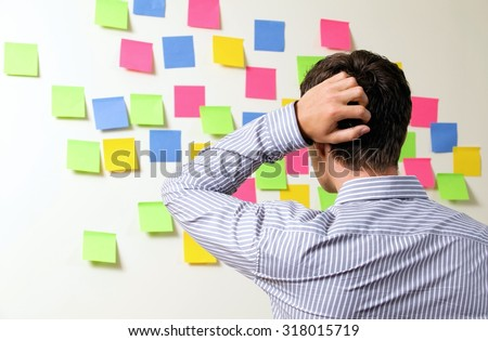 Businessman looking at wall of sticky notes with hands behind head - stock photo