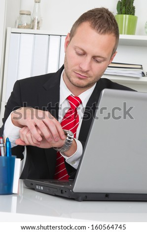 Businessman looking at watch with laptop - end of work - stock photo