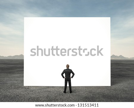 Businessman looking at white empty billboard in the desert - stock photo