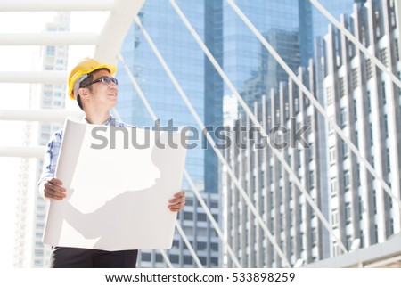 businessman looking away for new project while working at constructions site. Copy space.