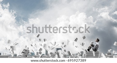 Businessman looking away while sitting on pile of documents among flying papers with cloudly sky on background. Mixed media.