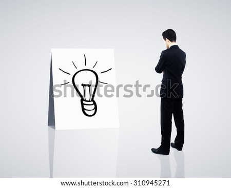 businessman looking card with drawing  lamp - stock photo