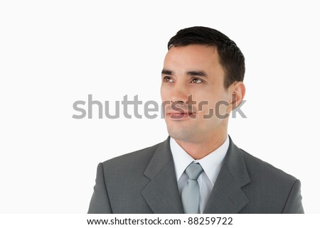 Businessman looking diagonally upwards against a white background