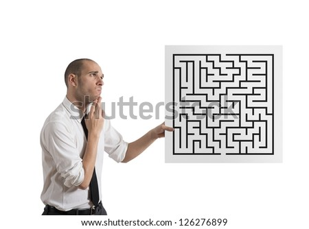 Businessman looking for a solution of a maze - stock photo