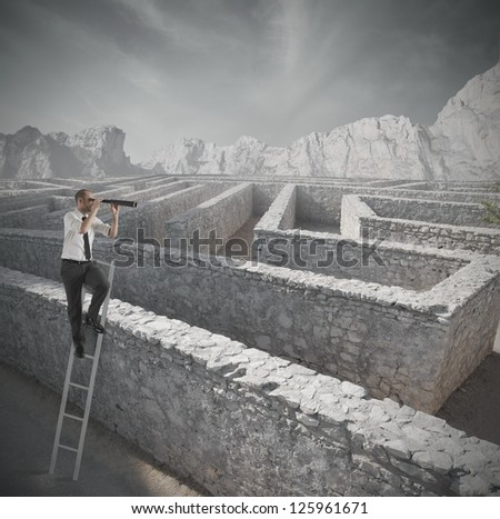 Businessman looking for the solution to the maze - stock photo