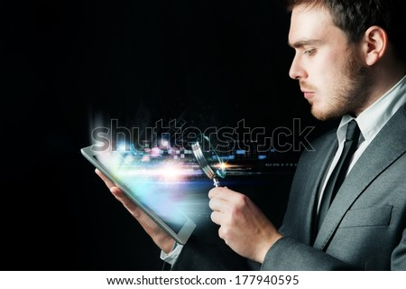Businessman looking for virus with a lens magnification - stock photo