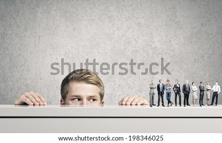 Businessman looking from under the table at businessteam - stock photo