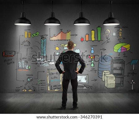 Businessman looking graphics drawn on a wall - stock photo
