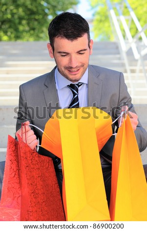 businessman looking in a bag after shopping - stock photo