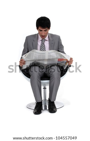 Businessman looking in shock at his newspaper - stock photo