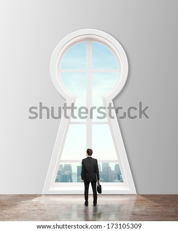businessman looking in window in form keyhole to city - stock photo