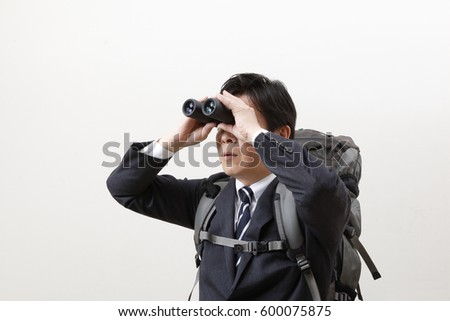 Businessman looking into binoculars