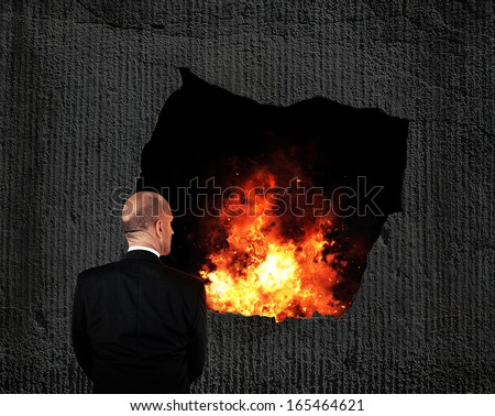Businessman looking into fire - burnout concept - stock photo