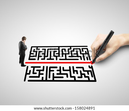 businessman looking like a hand drawing a labyrinth - stock photo
