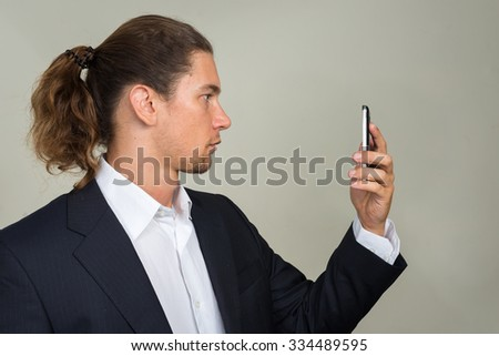 Businessman looking mobile phone - stock photo