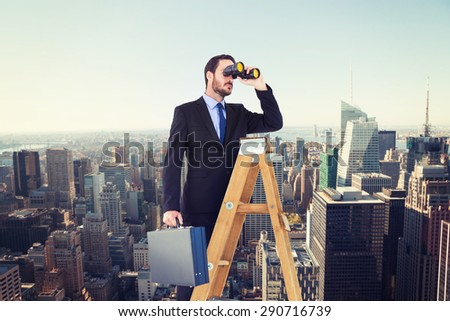 Businessman looking on a ladder against new york