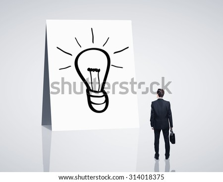 businessman looking on card with lamp - stock photo
